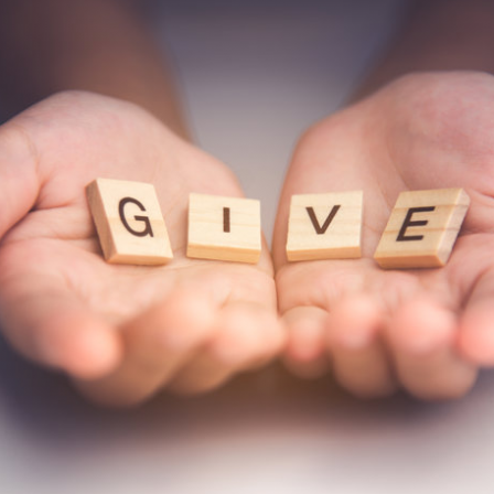 """hands holding Scrabble letters that spell """"give"""""""