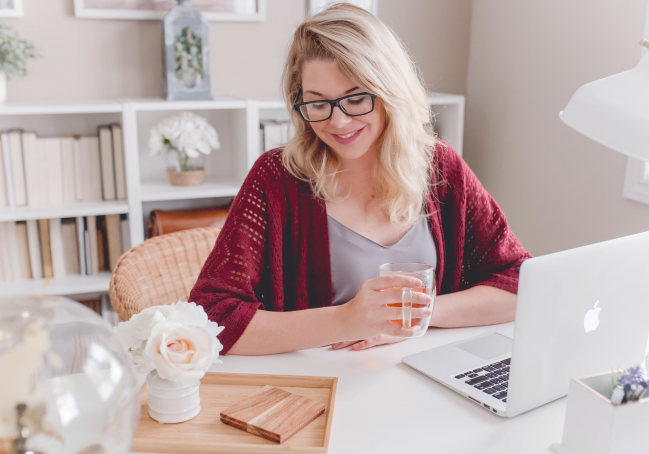 blond white woman in red sweater sitting at desk, holding mug, in front of laptop
